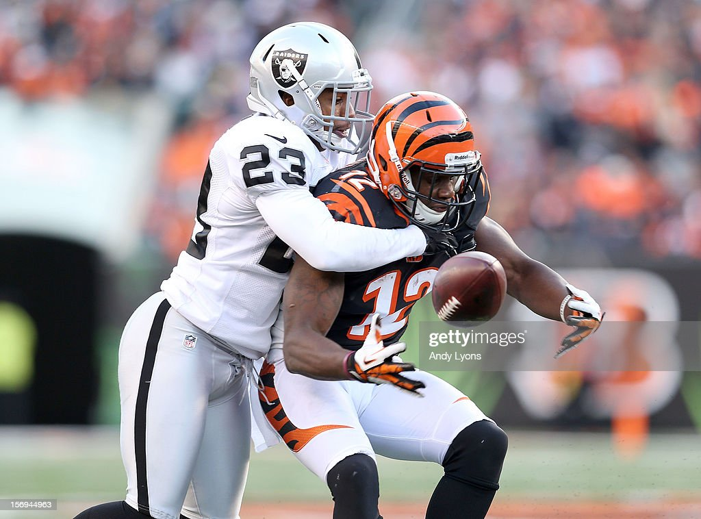 Mohamed Sanu #12 of the Cincinnati Bengals fumbles the ball while defended by Joselio Handon #23 of the Oakland Raiders during the NFL game at Paul Brown Stadium on November 25, 2012 in Cincinnati, Ohio.
