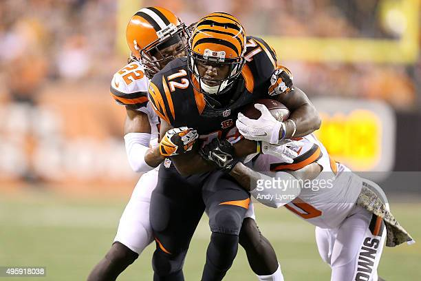 Mohamed Sanu of the Cincinnati Bengals is tackled by Tramon Williams of the Cleveland Browns and De'Ante Saunders of the Cleveland Browns during the...