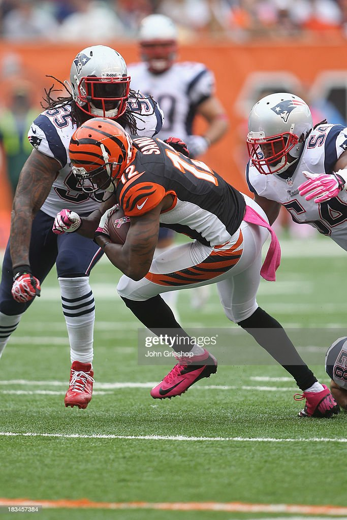 Mohamed Sanu #12 of the Cincinnati Bengals runs the ball upfield against Brandon Spikes #55 of the New England Patriots during their game at Paul Brown Stadium on October 6, 2013 in Cincinnati, Ohio. The Bengals defeated the Patriots 13-6.