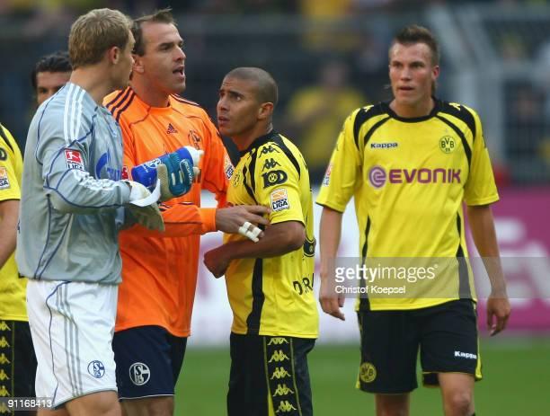 Mohamed Zidan of Dortmund has a disput with goalkeeper Manuel Neuer of Schalke and Mathias Schober after losing 01 the Bundesliga match between...