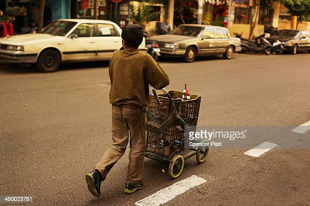 Mohammad a Syrian boy from the city of Daraa collects metal scrap to sell in a wealthy district of Beirut on November 16 2013 in Beirut Lebanon As...