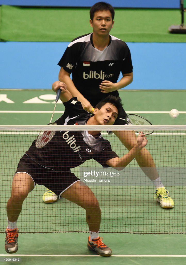 Mohammad Ahsan of Indonesia returns a shot as team mate <a gi-track='captionPersonalityLinkClicked' href=/galleries/search?phrase=Hendra+Setiawan&family=editorial&specificpeople=2237241 ng-click='$event.stopPropagation()'>Hendra Setiawan</a> watches on against Yong Dae Lee and Yeon Seong Yoo of Korea during day six of Badminton YONEX Open on June 15, 2014 in Tokyo, Japan.