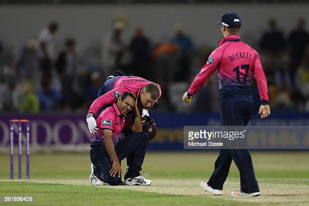 Mohammad Azharullah of Northants is consoled by wicketkeeper Adam Rossington after conceding the winning runs to Kumar Sangakkara of Surrey during...