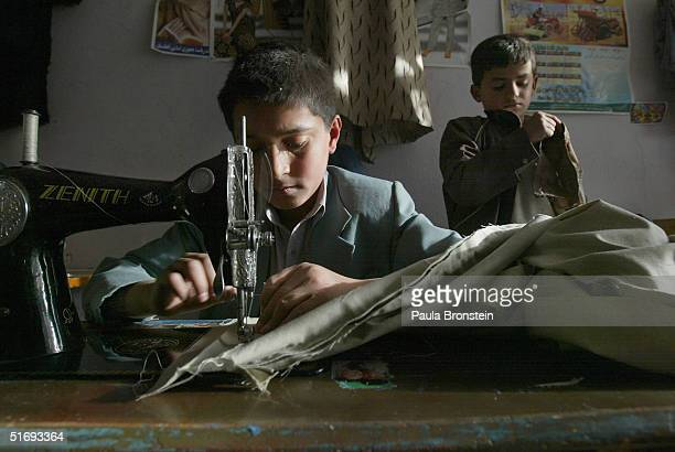 Mohammad Elais age 13 sews a pair of pants while Mustafa age 7 checks some stitching at the Sajaad Tailor shop November 5 2004 in Kabul Afghanistan...