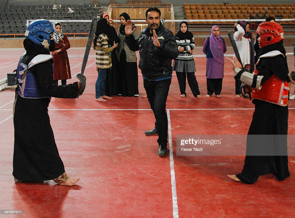 Mohammad Iqbal a martial art coach teaches Kashmiri Muslim girls Thang-ta, martial arts inside indoor stadium on December 16, 2013 in Srinagar, the summer capital of Indian administered Kashmir, India. As the number of crimes against women has risen in the region, girls from different age groups and backgrounds have taken up martial arts and other self defence courses to thwart attackers. Many believe after the barbaric rape and murder of a para-medic student last year on this day in the Indian capital of New Delhi, women in the Muslim majority state have taken to various martial arts forms like Thang-ta, a weapon-based Indian Martial art for protection.