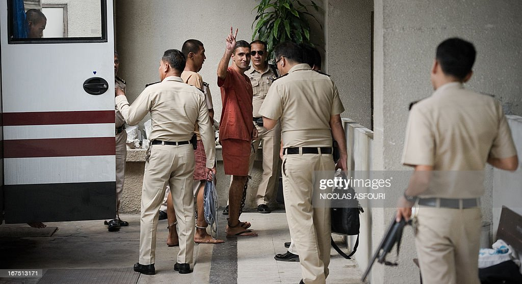 Mohammad Khazaei (C), 42, an Iranian suspected of involvement in the February 2012 blasts gestures as he disembarks from a prison bus upon his arrival at the southern criminal court in Bangkok on April 26, 2013. Two Iranians will testify in their trial over an alleged botched bomb plot against Israeli diplomats in Bangkok. AFP PHOTO / Nicolas ASFOURI