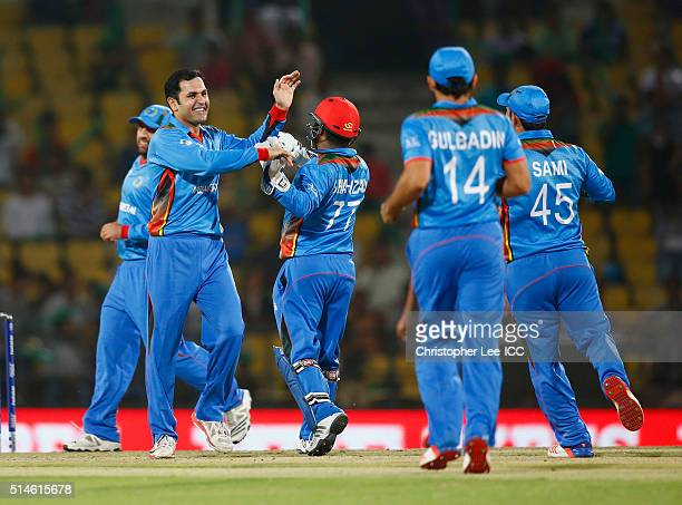 Mohammad Nabi of Afghanistan celebrates taking the wicket of Babar Hayat of Hong Kong with his team mates during the ICC Twenty20 World Cup Round 1...
