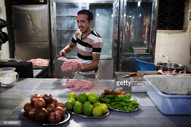 Mohammad prepares meat in a kebab restaurant in the Sheikh Najjar industrial zone near Syria's northern city of Aleppo on September 20 2013 War had...