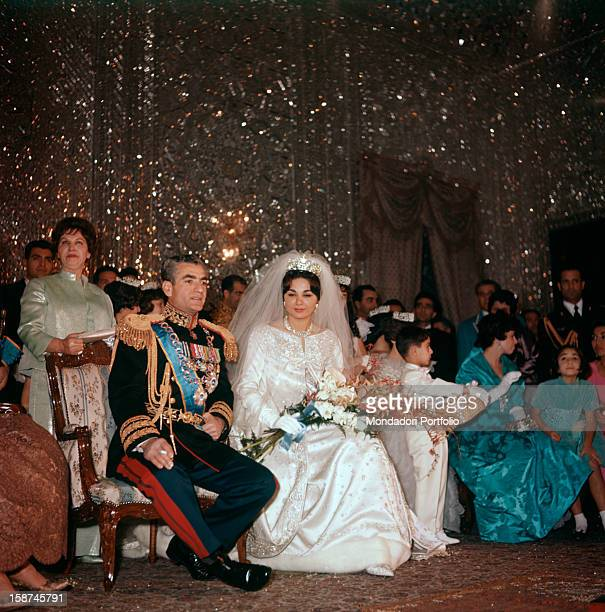 Mohammad Reza Pahlavi Shah of Iran is seated next to her third wife Farah Diba on the day of their marriage her gown is by Yves St Laurent and on her...