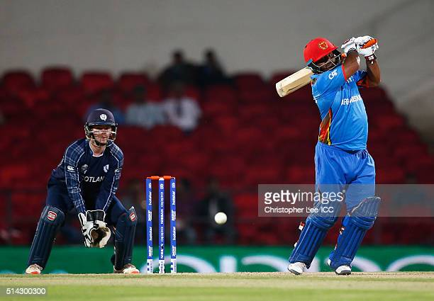 Mohammad Shahzad of Afghanistan in action with wicket keeper Matthew Cross of Scotland during the ICC Twenty20 World Cup Group B match between...