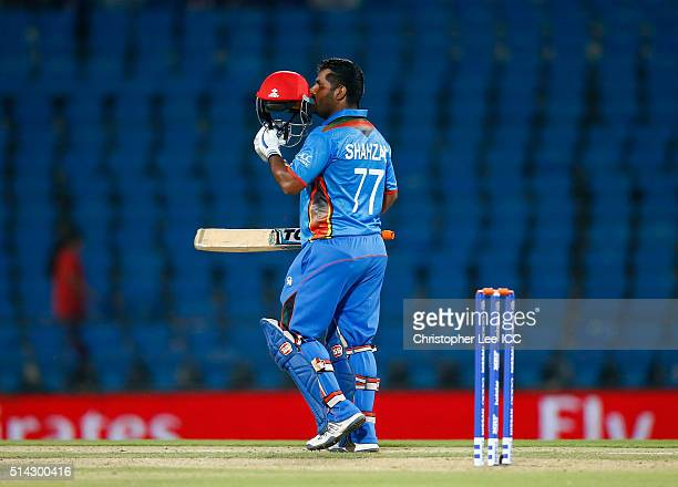 Mohammad Shahzad of Afghanistan kisses the emblem on his helmet as he celebrates his 50 runs during the ICC Twenty20 World Cup Group B match between...