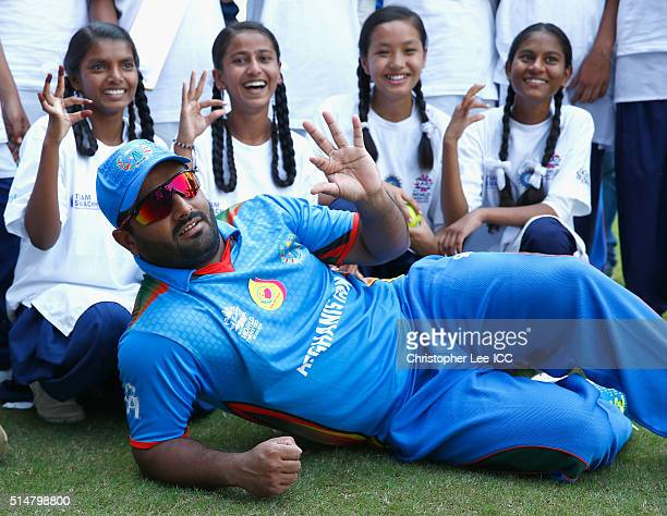 Mohammad Shahzad of Afghanistan puts up the 'Bowl Out Polio' sign with local kids during the ICC Cricket For Good and Team Swachh cricket clinics in...