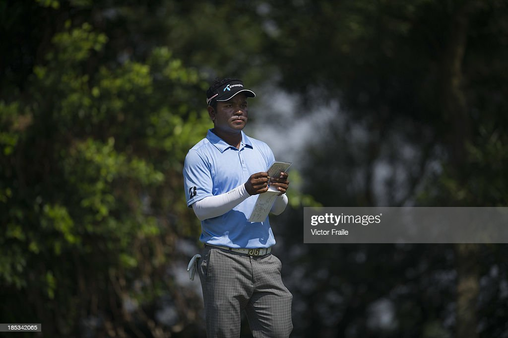 Mohammad Siddikur of Bangladesh checks his yardage book on the 6th tee during day three of the Venetian Macau Open at Macau Golf and Country Club on October 19, 2013 in Macau, Macau.