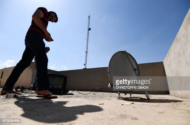 Mohammad Turki installs a satellite dish on the rooftop of a house in eastern Mosul's AlQahira district on April 15 2017 Since Iraqi forces seized...
