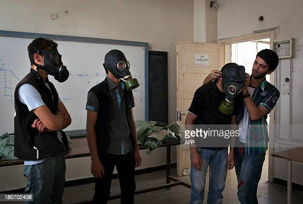 Mohammad Zayed an Aleppo University student shows Syrian citizens hows to put on gas masks as he instructs them with rudimentary means of how to...