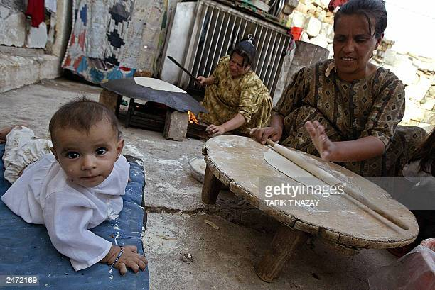Mohammed a six monthold Kurdish boy lies near his mother in the Northern Iraqi town of Mossoul 03 September 2003 His mother is cooking the daily...