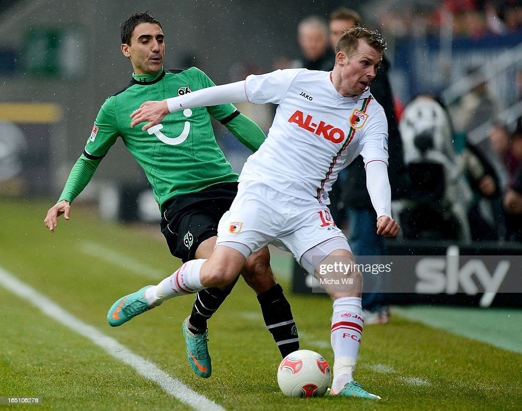 Mohammed Abdellaoue (L) of Hannover collides with <a gi-track='captionPersonalityLinkClicked' href=/galleries/search?phrase=Jan-Ingwer+Callsen-Bracker&family=editorial&specificpeople=758385 ng-click='$event.stopPropagation()'>Jan-Ingwer Callsen-Bracker</a> of Augsburg which resulted in his colliding with advertising hoardings next to the pitch during the Bundesliga match between FC Augsburg and Hannover 96 at SGL Arena on March 30, 2013 in Augsburg, Germany.