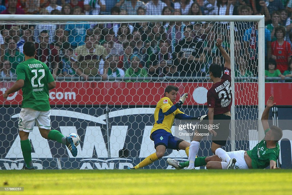 Mohammed Abdellaoue of Hannover (2nd R) scores the second goal against <a gi-track='captionPersonalityLinkClicked' href=/galleries/search?phrase=Sokratis+Papastathopoulos+-+Soccer+Player&family=editorial&specificpeople=4426771 ng-click='$event.stopPropagation()'>Sokratis Papastathopoulos</a> (L), Sebastian Mielitz (C) and <a gi-track='captionPersonalityLinkClicked' href=/galleries/search?phrase=Sebastian+Proedl&family=editorial&specificpeople=4409096 ng-click='$event.stopPropagation()'>Sebastian Proedl</a> (R) of Bremen ring the Bundesliga match between Hanover 96 and SV Werder Bremen at AWD Arena on October 2, 2011 in Hannover, Germany.