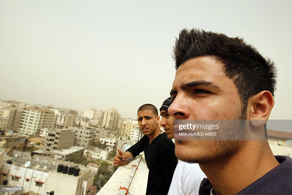 Mohammed Abo Ramdan (R) looks out on Gaza City on April 8, 2013 with his friends Ayman al-Sayed (L) and Tarq Al-Naqeb (R), both of whom had their heads shaved after Hamas security forces in Gaza rounded them up with other young men and forced them to get a haircut on grounds of inappropriate hairstyles. Some of the youths have even been beaten for styling their hair in a way deemed unacceptable to Gaza's ruling Islamist movement, or wearing low-hung trousers, the Palestinian Centre for Human Rights said.