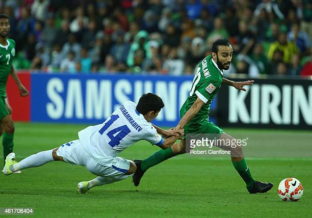 Mohammed Al Sahlawi of Saudi Arabia is challenged by Shukhrat Mukhammadiev of Uzbekistan during the 2015 Asian Cup match between Uzbekistan and Saudi...