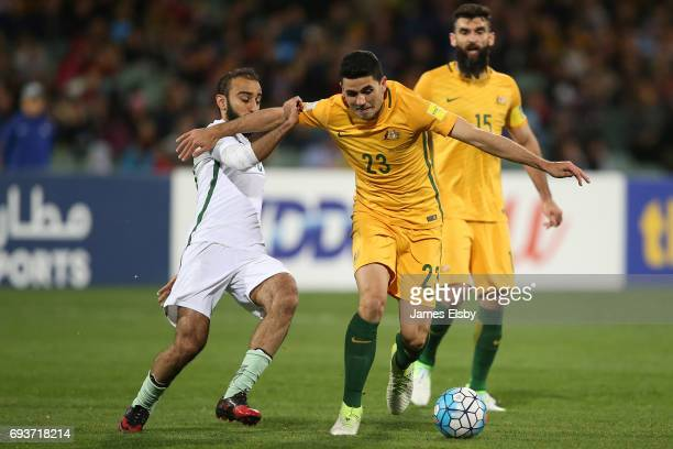 Mohammed Al Sahlawi of Saudi Arabia tackles Tomas Rogic of Australia during the 2018 FIFA World Cup Qualifier match between the Australian Socceroos...
