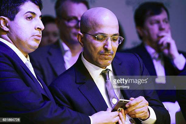 Mohammed AlJadaan Saudi Arabia's finance minister right looks at a mobile device whilst sitting in the audience during a panel session at the World...