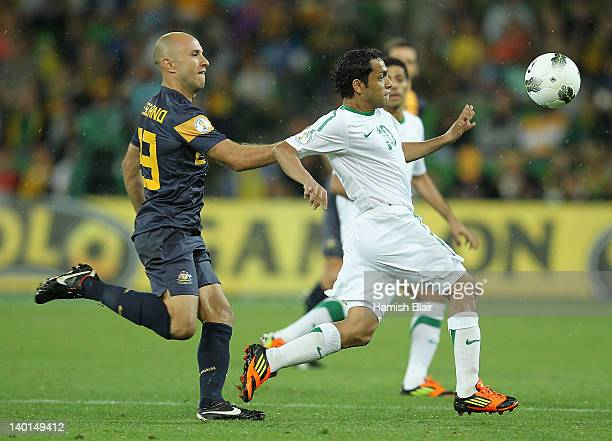 Mohammed Bandar Alshehri of Saudi Arabia contests with Mark Bresciano of Australia during the Group D 2014 FIFA World Cup Asian Qualifier match...