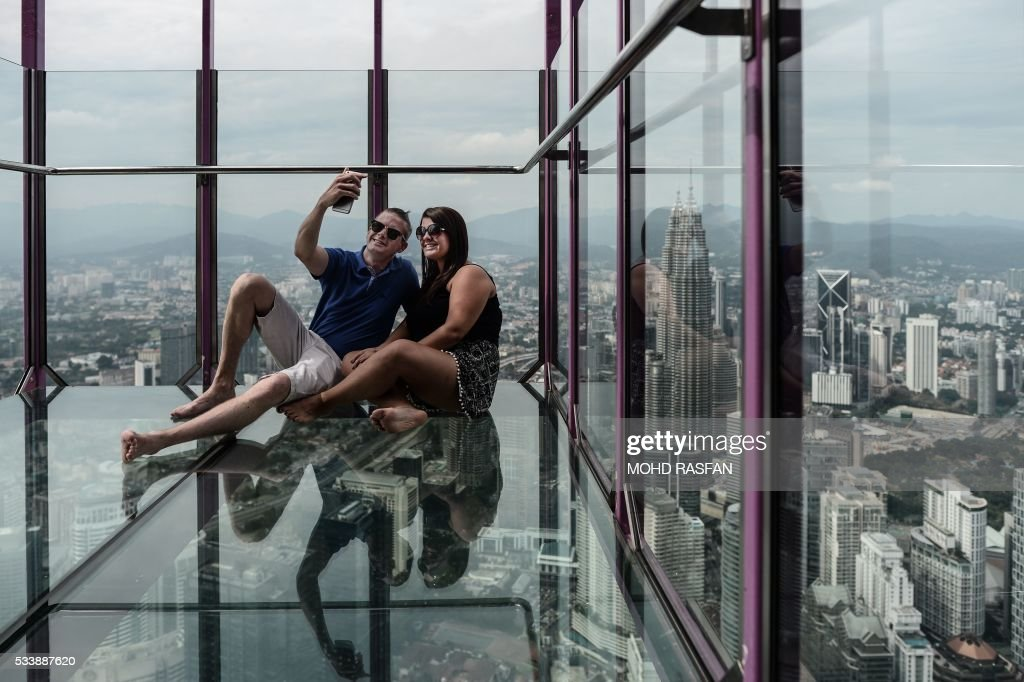 Mohammed Ehtsham (L) and Maham Ehtsham (R) from England take pictures with the panoramic view of the city from the Sky Box at KL Tower, the world's seventh tallest telecommunications tower, in Kuala Lumpur on May 24, 2016. Officially opened on May 20, the Sky Box has been the latest attraction for tourists arriving to the Malaysian capital. It stands 300 metres above ground and can fit six people at any one time, and offers spectacular views of the Kuala Lumpur skyline, including the iconic Petronas Twin Towers. / AFP / MOHD