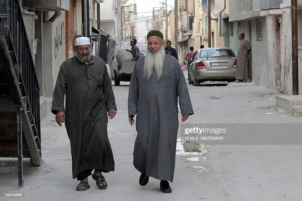 Mohammed (L), Father of Jordanian of Palestinian origin Salafist, Mahmud Abdelal, who blew himself up in the Syrian city of Daraa last month, walks with his son's father-in-law and top Salafist leader in Jordan, Abed Shehadeh, known as Abu Mohammad Tahawi (R) in the Baqaa Palestinian refugee camp, north of Amman, on November 1, 2012. Tahawi said more than 250 Jordanian jihadists are now in Syria to fight and that 13 others have been killed there.