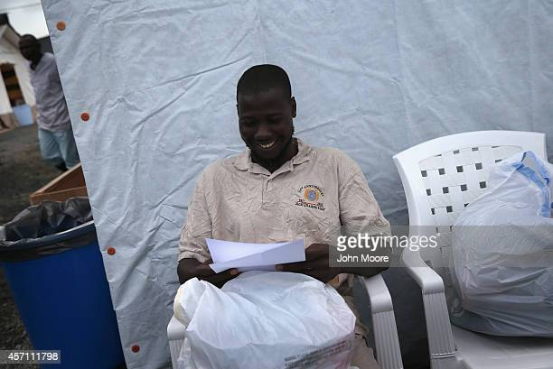 Mohammed Jan Jallo smiles while looking over a letter from Doctors Without Borders labeling him as Ebolafree folowing his recovery at the MSF...