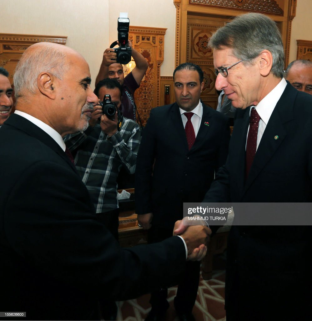 Mohammed Megaryef president of Libya's ruling General National Congress shakes hands with Italian Foreign Minister Giulio Terzi upon the latter's...