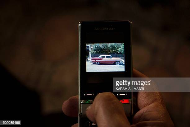 Mohammed Mohiedin Anis or Abu Omar a 69yearold Syrian classic car collector holds a mobile phone showing a photo of one of his cars in the rebel held...