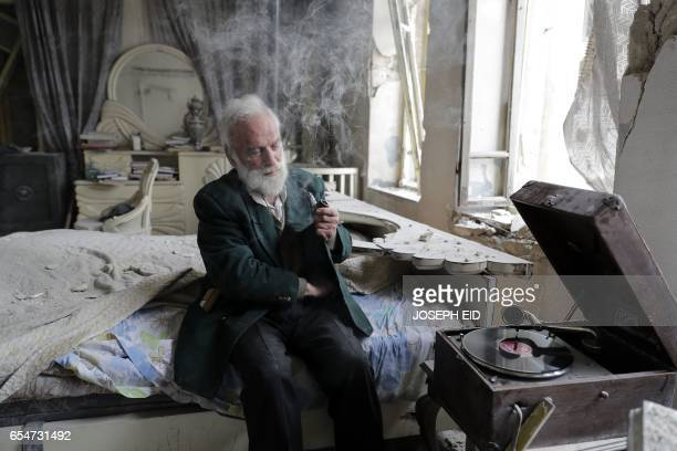 Mohammed Mohiedin Anis or Abu Omar lights his pipe as he sits in his destroyed bedroom listening to music on his vinyl player gramophone in Aleppo's...