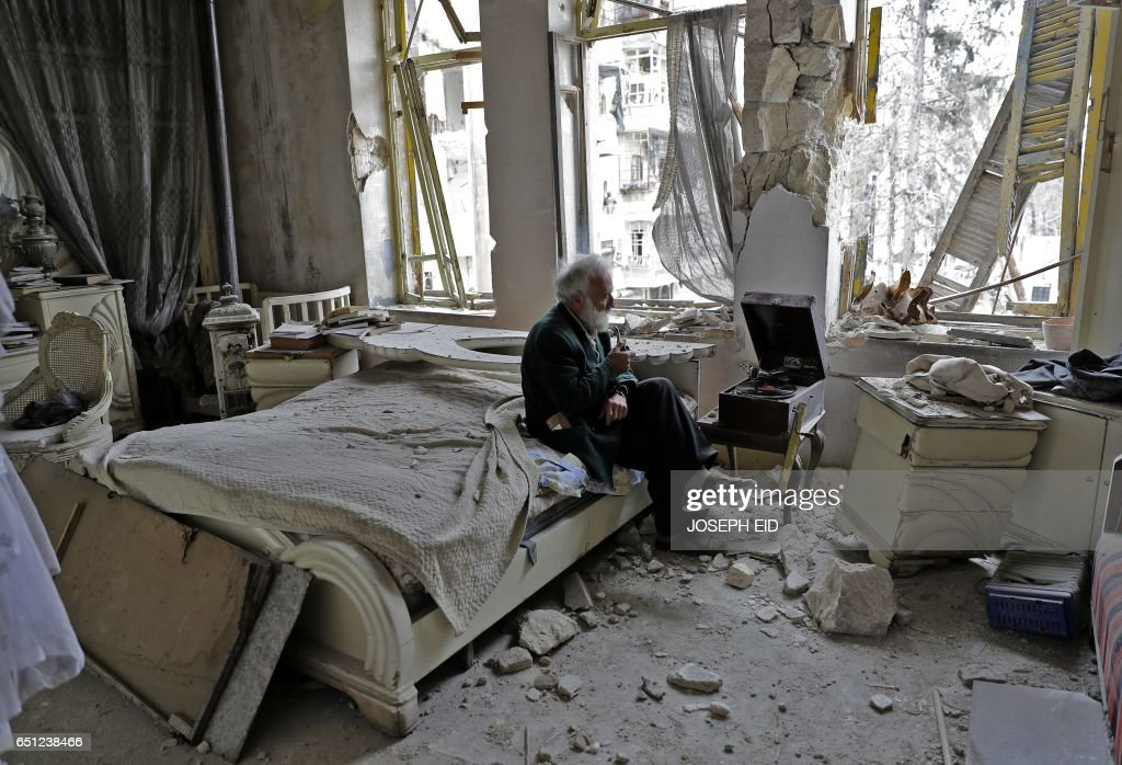 TOPSHOT - Mohammed Mohiedin Anis, or Abu Omar, 70, smokes his pipe as he sits in his destroyed bedroom listening to music on his vinyl player, gramophone, in Aleppo's formerly rebel-held al-Shaar neighbourhood. /