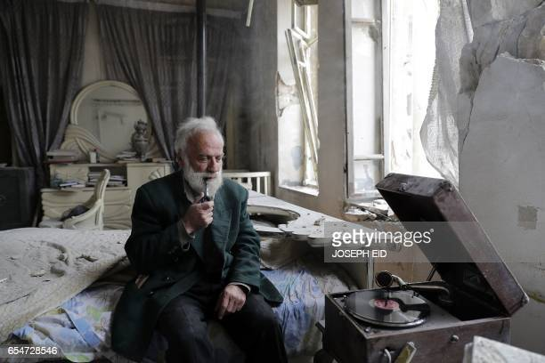 Mohammed Mohiedin Anis or Abu Omar smokes his pipe as he sits in his destroyed bedroom listening to music on his vinyl player gramophone in Aleppo's...