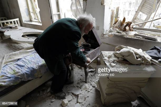 Mohammed Mohiedin Anis or Abu Omar winds his vinyl player gramophone as he sits in his destroyed bedroom in Aleppo's formerly rebelheld alShaar...