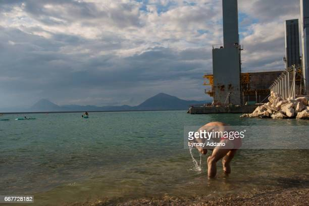 Mohammed Reza an Iranian refugee trying to make his way to Italy swims at the port with other Afghan migrants after a day of failed attempts to sneak...