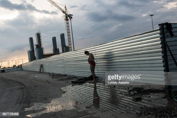 Mohammed Reza an Iranian refugee trying to make his way to Italy bathes at the port with other Afghan migrants after a day of failed attempts to...