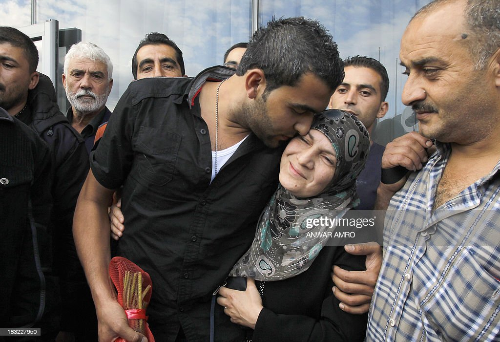 Mohamud Ahmed (C), a Lebanese survivor of the migrant shipwreck in Indonesia last week, is welcomed by relatives as he arrives at Beirut airport on October 6, 2013. Lebanese asylum-seekers who died when a boat sank off Indonesia were the victims of people smugglers who prey on them and Syrian refugees seeking to better their lives.