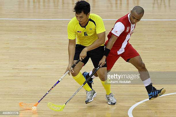 Mohd Haidir Mohd Hilmi Hafidz of Malaysia and Hazmi Hasan of Singapore challenge for the ball during the World University Championship Floorball...