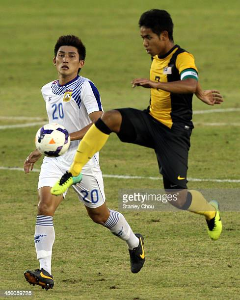 Mohd Irfan Fazail of Malaysia battles with Khouanta Sivongthong of Laos during the Men's Football Competition during the 2013 SEA Games at the Zeyar...