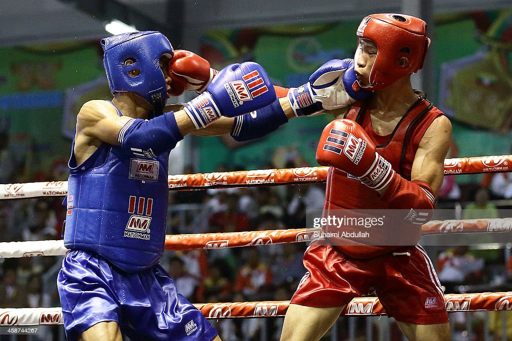 Mohd Lokman Akimi (red) of Malaysia fights Ngo Trieu Nhat Nguyen (blue) of Vietnam during the male muay 51kg division weight bout at the Wunna Theikdi Boxing Centre during the 2013 SEA Games on December 21, 2013 in Nay Pyi Taw, Burma.