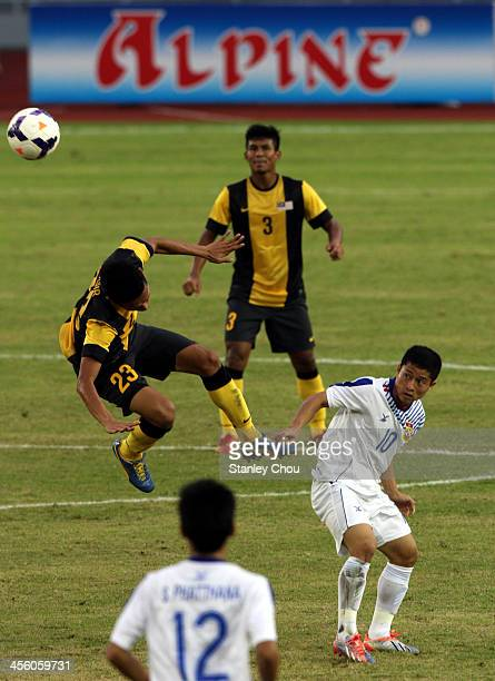 Mohd Nasir of Malaysia battles with Souk Aphone Vongchiengkham of Laos during the Men's Football Competition during the 2013 SEA Games at the Zeyar...
