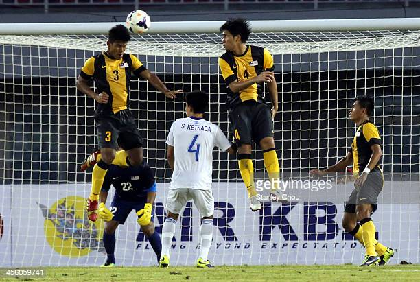 Mohd Saad Shahrul of Malaysia heads the ball while Mohd Fadhli and Kitsada Souksavanh of Laos looks on during the Men's Football Competition during...
