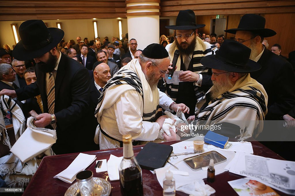 Mohel Manachem Fleischmann (C) concludes the circumcision ceremony of baby infant Mendl Teichtal at the Chabad Lubawitsch Orthodox Jewish synagogue on March 3, 2013 in Berlin, Germany. Germany's parliament, the Bundestag, passed a law affirming the legality of circumcision in December after a Cologne court called the practice into question in May of 2012, a ruling that sparked outrage among Germany's Jewish and Muslim population.