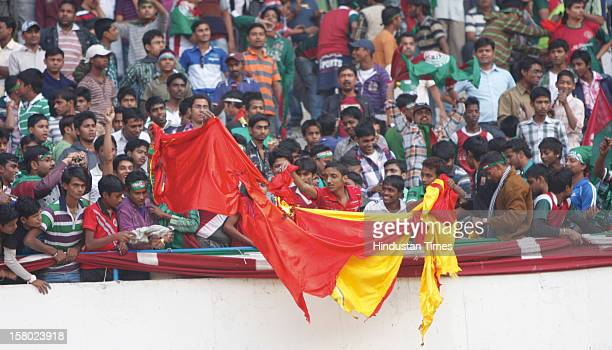 Mohun Bagan supporters burning an East Bengal flag in the stadium during ILeague Match between Mohun Bagan and East Bengal on December 9 2012 in...