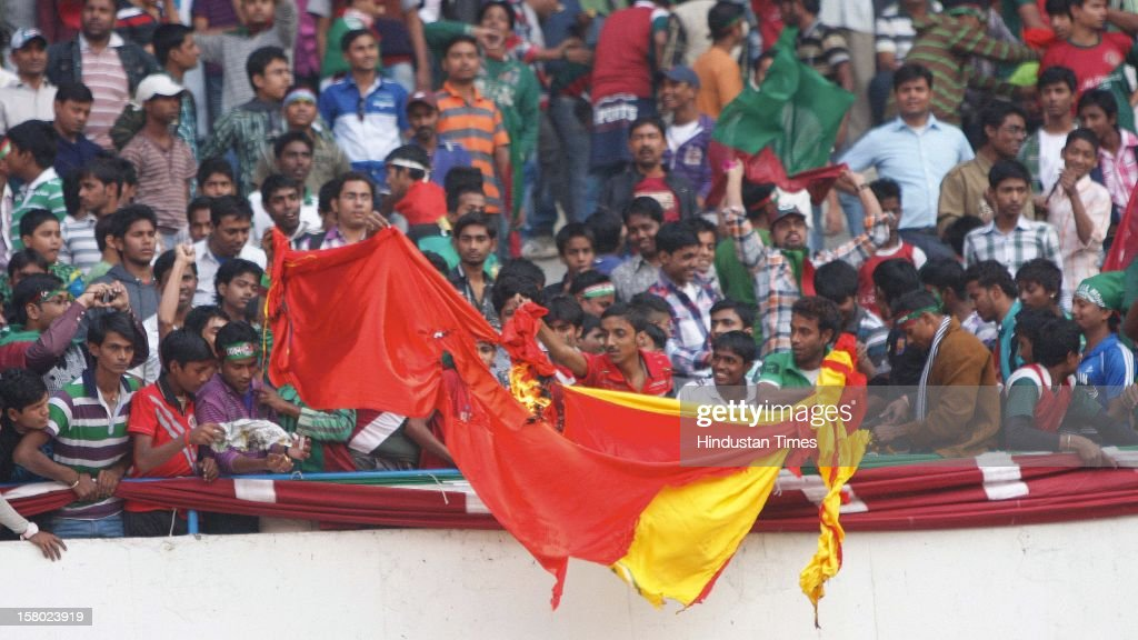 Mohun Bagan supporters burning an East Bengal flag in the stadium during I-League Match between Mohun Bagan and East Bengal on December 9, 2012 in Kolkata, India. The casualties included 40 spectators and 20 policemen who were injured in the scuffle, police sources said.