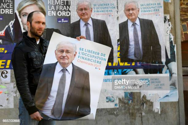 Moise a supporter of French presidential election candidate for the Solidarite et Progres party Jacques Cheminade poses with electoral posters that...