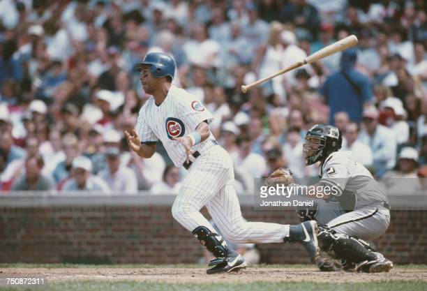 Moises Alou in fielder for the Chicago Cubs releases his bat after a hit as Mark Johnson catcher for the White Sox looks on during the Major League...