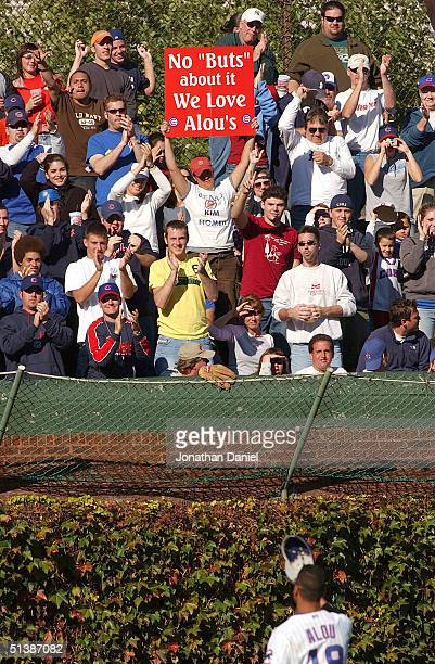 Moises Alou of the Chicago Cubs is greeted by cheers and a sign by fans in the left field bleechers during the final game of the season against the...